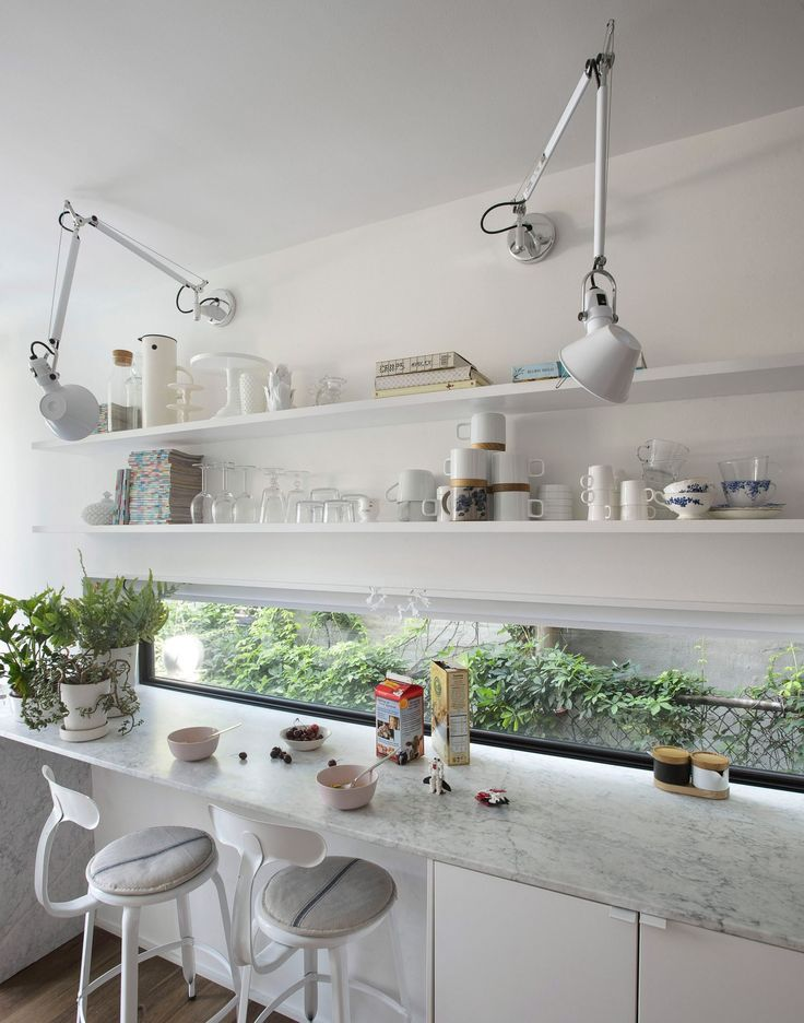 The kitchen area features white cabinets and Carrara marble countertops. Daylight is provided by a long narrow window that runs along one of the counters and a glazed door that gives access to the backyard.