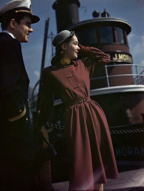 St. Louis, Missouri July 1945    Model is standing in front of a riverboat, wearing a red wool dress with wide bishop sleeves and a new wide soft skirt, silver buttons that descend in threes by Carlyle, hat by Betmar, handbag by I. Miller.