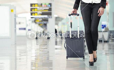 Молодая женщина тянет багаж в аэропорту, заделывают сексуальные ноги — Стоковое фото © stokkete #16769679
