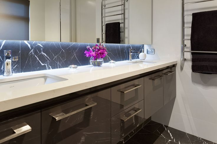 Floating, custom designed ensuite cabinetry with mirrored overhead cabinets for additional storage by Urbane Projects, Perth.