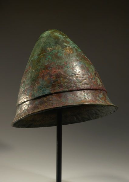 Front; Pilos helmet. Circa. 4th to 3rd Century B.C. Measurement; h. 23.00 cm. Style; Pilos  Materials; Bronze alloy, textile.  Information; Made in two pieces with a broad offset concave brim and internal loops to attach chin straps. The internal lining is removed.  Providence; (AG 519/H 172) of Axel Guttmann (1944 to 2001), Berlin, Krefeld 1991. Published; J. Eisenberg, Art of the Ancient World, 2010, no. 100. Reference; HMQ49 COPYRIGHT © Royal Athena