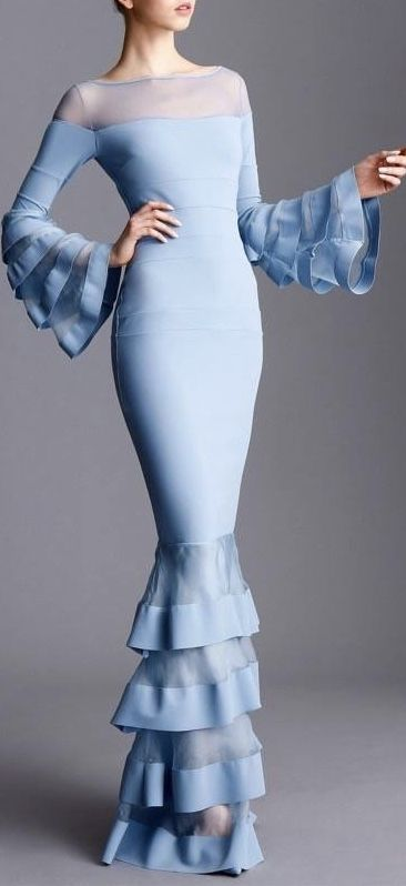 Light blue fitted gown with sheer shoulders and neck line and ruffles on the large bell sleeves and bottom of the skirt