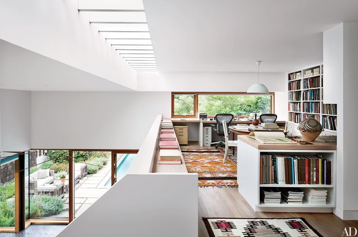 The mezzanine office of a Hamptons home updated by Christoff:Finio Architecture features an Arne Jacobsen pendant light from Louis Poulsen Lighting, which descends from the ceiling, while a golden Moroccan kilim and a Navajo rug, both midcentury, decorate the floor.