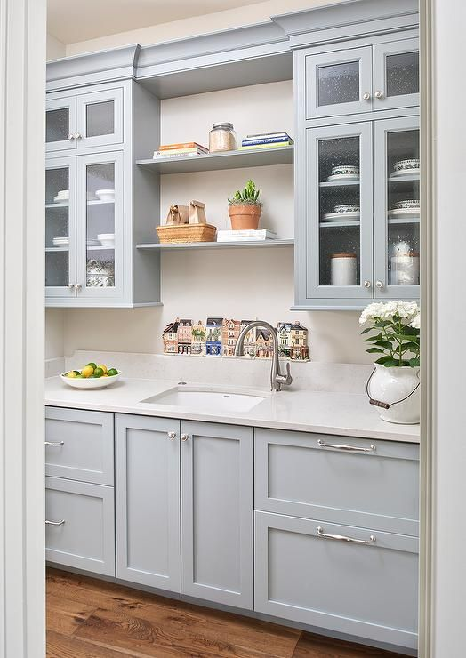 Blue butler's pantry features blue shaker paired