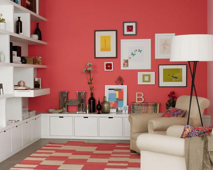 Donnez de la profondeur à votre salon avec le rouge. Le mur d'un corail lumineux donne de la profondeur et structure l'espace de ce salon tout en créant le contraste avec la bibliothèque blanche intégrée.