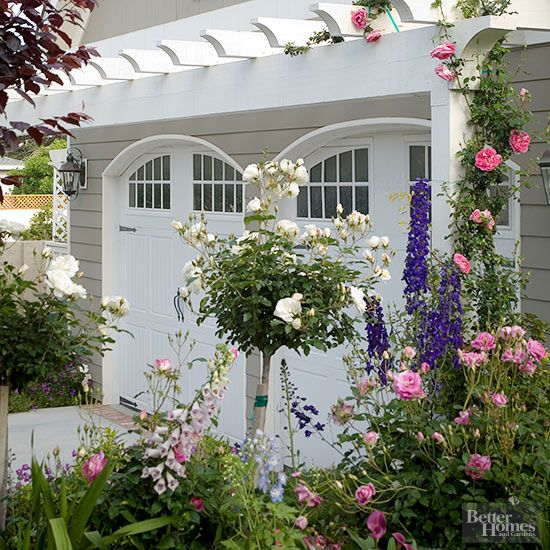 An entrancing garage entrance accented with rooster-tail rafters meant to support clambering roses captivated BHG readers' attention. Opt for similarly distinctive doors and architecturally apt details to ensure your garage reads as part of your house rather than a utilitarian afterthought./