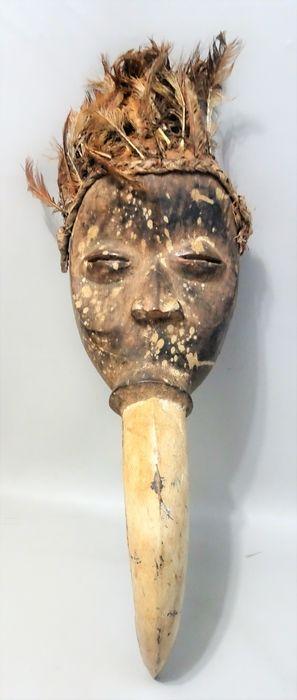 Oude Ge Gon snavel masker - DAN - Ivoorkust Liberia  Dan Ge Gon maskerIvoorkust LiberiaHout kaolien verenca. 59 cm x 17 cmMidden van de 20e eeuwDit type masker met een lange snavel uit uit het zelfde stuk gehouwen genaamd 'Ge Gon' (of Gegon) toont een gestileerde neushoornvogel. Zeer mooi voorbeeld van een subtiele menging van menselijke en dierlijke kenmerken. Het is in hard hout gesneden en geverfd wit aan de voorkant en met veren op de top.Gemaskerde dansers die met maskers zoals de…