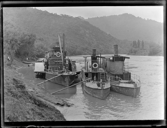 Two riverboats, one being the [Wairua?], and an unidentified paddle steamer moored a bank of the Whanganui River, with forest covered hills ...