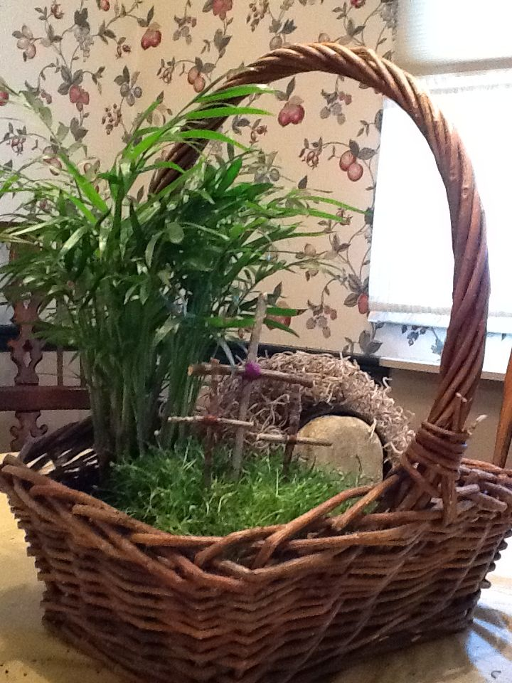 """Resurrection garden basket. I bought my basket, plastic liner and plants at our local garden center. I chose a palm plant and a low growing grass type. I used a black plastic 3"""" pot laid it on its side and covered it with spanish moss for the tomb.  Placed a rock at the opening and extra small ones as a path. We picked sticks up in the yard and broke them to size and used colored thread to secure them together."""