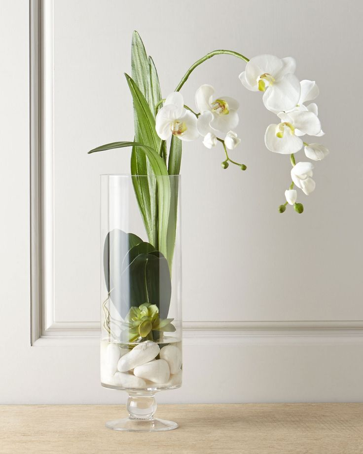 "John Richard Collection - Handcrafted faux orchid is displayed in a glass vase with rolled marble stones and acrylic ""water."""