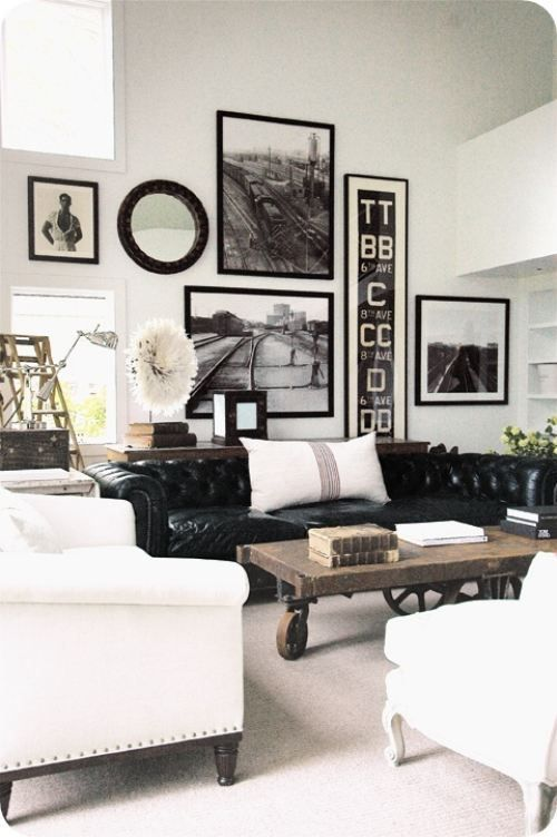 Black Leather Chesterfield Sofa, White Slipcovered Chairs, and B&W Art Wall create a Modern and Masculine Room.