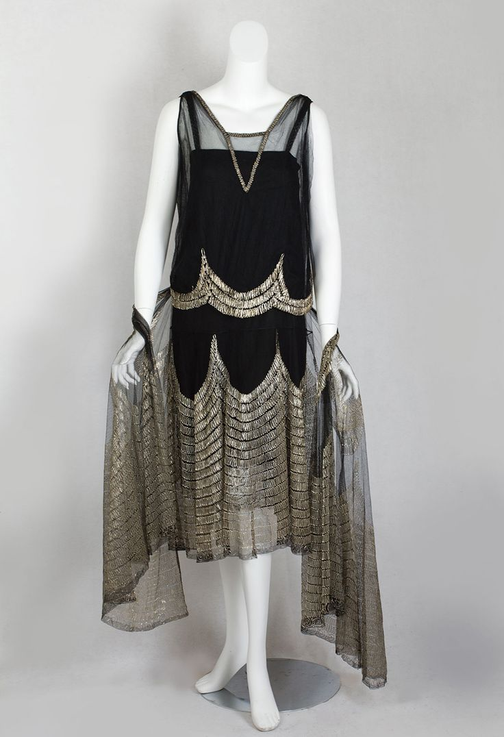 Flapper dress with metallic cord embroidery and matching shawl, c.1925. There are three pieces: a black satin slip covered with layers of black silk chiffon and black net; a double layer net bodice shell; and a matching shawl. The gold metallic scallops infuse the glorious ensemble with an incandescent beauty