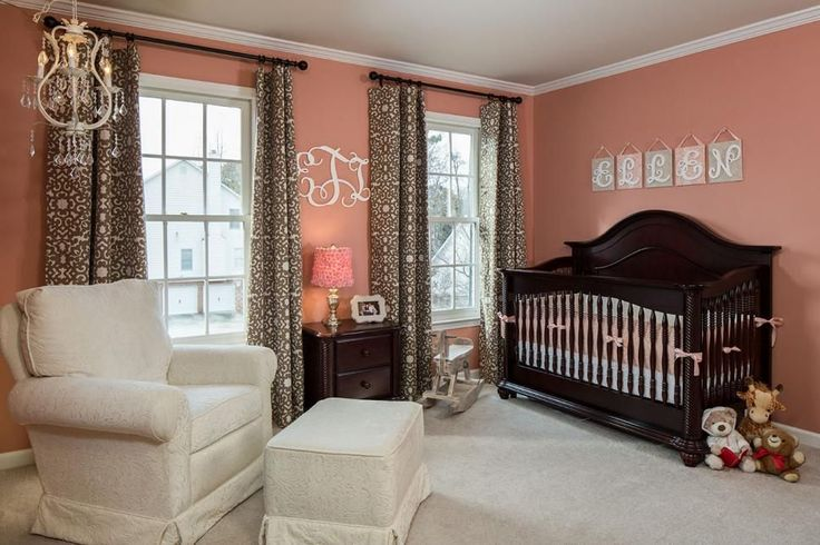 Warm, peachy-rose walls contrast with the dark wood crib and side table. An ivory armchair with a matching stool sits underneath a feminine, white chandelier. Brown and white patterned curtains make a funky statement.