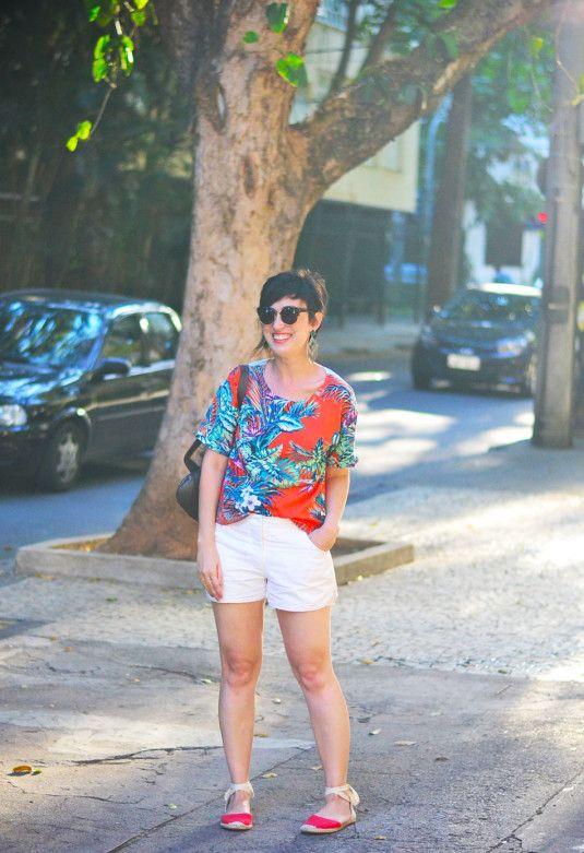 blusa laranja estampada de folhagens tipo palmeiras verdes, azuladas e roxas, short branco, brinco de franjas e triângulos verdes, espadrilhe baixa vermelha