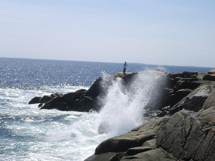 A smaller wave crashing up against the rocks at Peggys Cove Nova Scotia