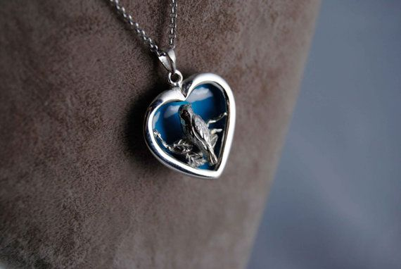 925 Silver Handmade Bird in the Heart Necklace  The Bird stays on the branches of an ancient tree which is located in the middle of the desperate womans heart.  It is finished with White Gold Plating and behind the bird you can see the blue sky with the white clouds. Which are painted using warm enamel.  Behind the necklace a pair of hand carved flowers can be seen.   The chain on the necklace is 50cm. (Can be customised for your special desires)  ______________  As always we offer free…