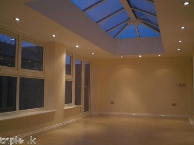 Roof lantern with downlighters. Looks quite a modern take, but then you have to consider you have less ceiling space for repositioning. A central chandelier would make a good addition here.