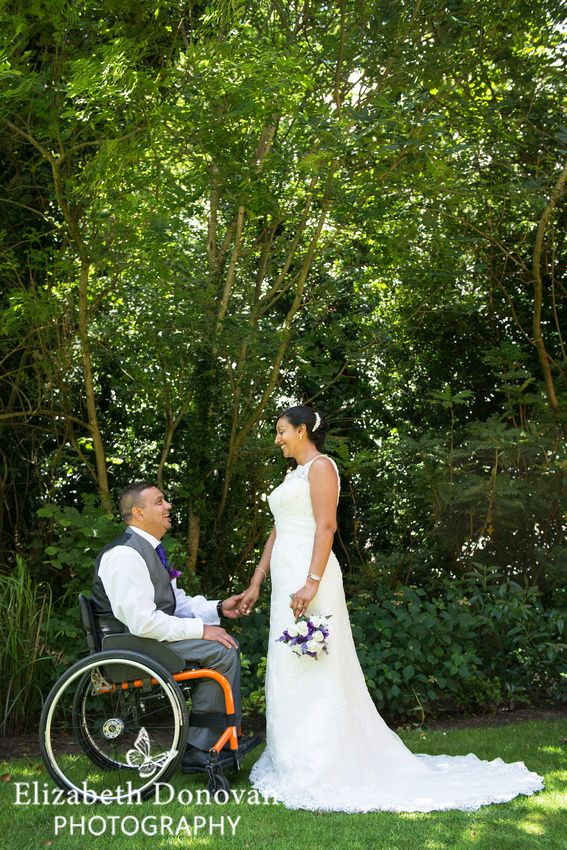 bride and groom holding hands, bride and groom sharing a moment, bride looking at groom, wheelchair wedding couple, purple and white flowers