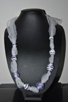 Collana realizzata con tulle bianco e perle in carat da parati viola.   Necklace made of white tulle and pearls in purple wallpaper.