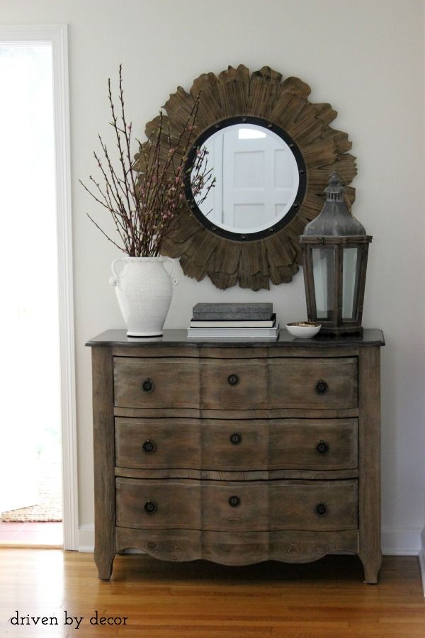 Weathered foyer chest || ceramic jug with flowering branches || lantern || round wood and iron mirror