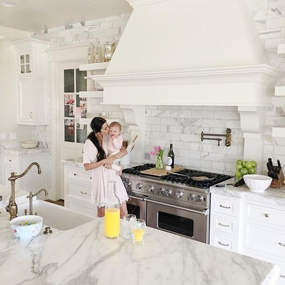This is a gorgeous white kitchen! The marble backsplash and the custom range hood are my favorite parts.