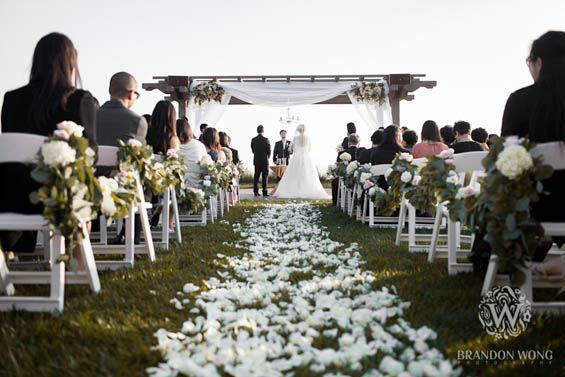 An outdoor winter oceanfront wedding with a floral lined aisle at Terranea Resort in Rancho Palos Verdes | Southern California luxury hotel wedding venues by the beach (Brandon Wong Photography)