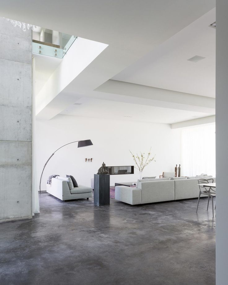 Concrete floors give stark industrial style to this modern living area that features simple, clean lines and minimal furnishings. A swooping arc lamp breaks up the space with a hint of movement.