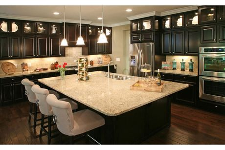 Tailored Chairs At An Island With Black Cabinets The