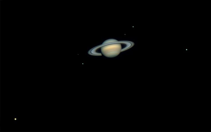 There are many pictures with a much larger view of Saturn than this one here, but zoom in and you'll see Saturn surrounded by six (6) of its moons! :D