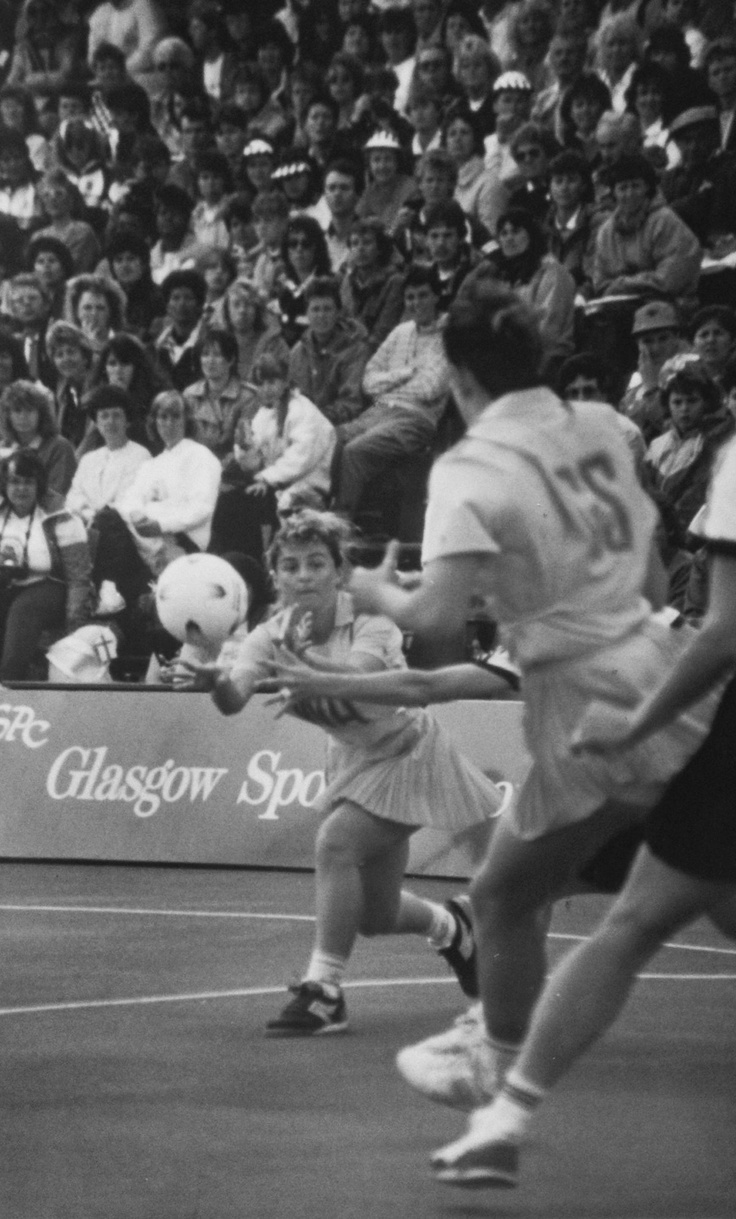 "Netball News 1987: ""Janelle Peterson shoots the ball to Vicki Wilson (GS) at 7th World Tournament."""