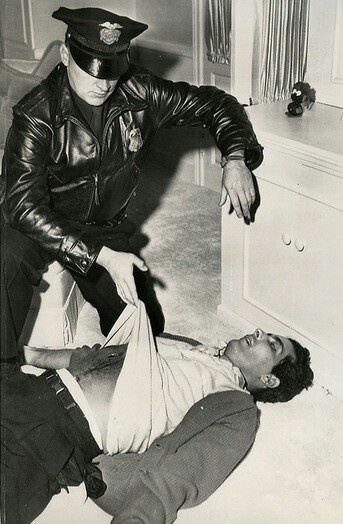 An LAPD officer inspects Johnny Stompanato's body in Lana Turner's pink bedroom on Bedford Drive.  The house was later owned by Mary Tyler Moore & Grant Tinker & still stands with virtually no modifications.