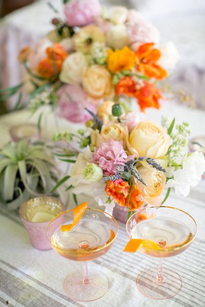 Bright pops of orange in the flowers add a modern vibe to the soft peach and ivory tones of the flowers.