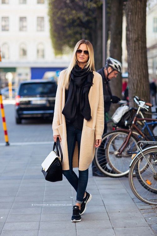 Master the effortlessly chic look in a beige coat and navy skinny jeans. Navy athletic shoes will give your look an on-trend feel.  Shop this look for $178:  http://lookastic.com/women/looks/sunglasses-scarf-coat-satchel-bag-skinny-jeans-athletic-shoes/4253  — Brown Sunglasses  — Navy Scarf  — Beige Coat  — Black and White Leather Satchel Bag  — Navy Skinny Jeans  — Navy Athletic Shoes