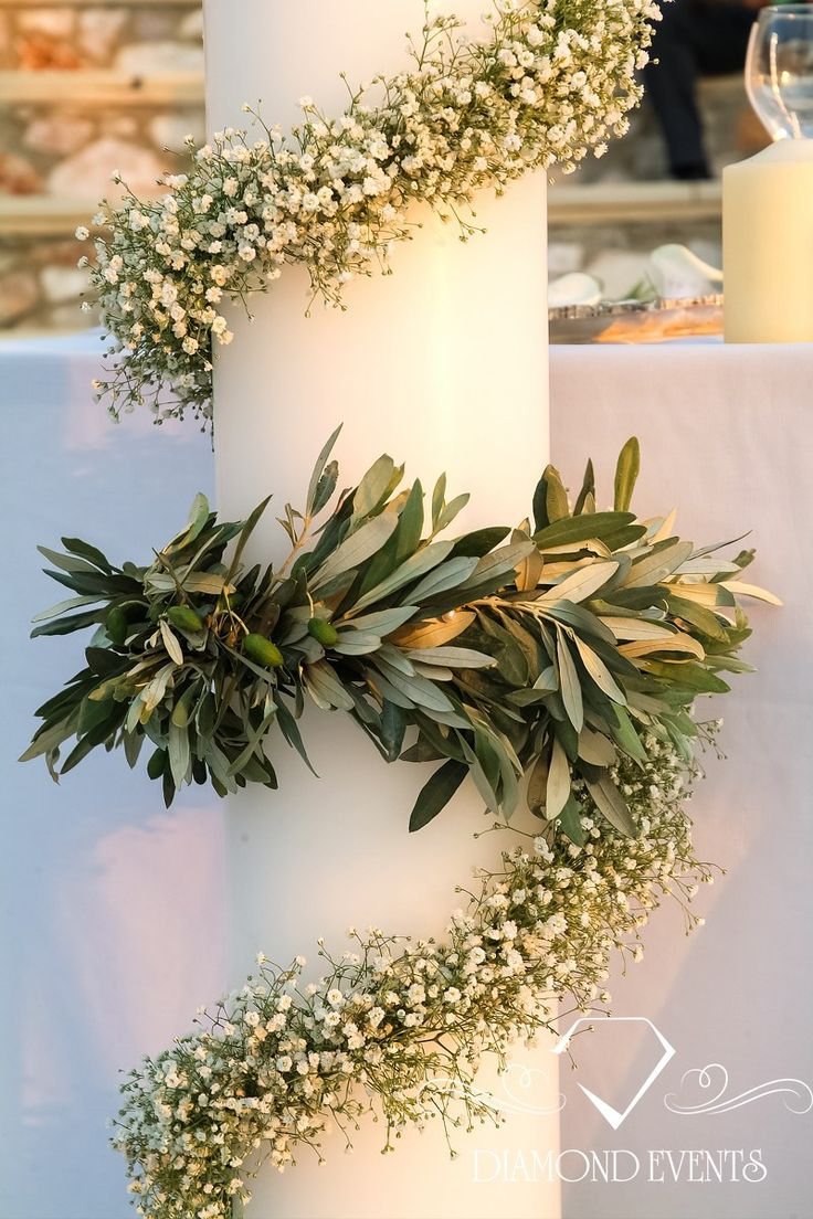 Wedding candle decorated with olive leaves and gypsophilia. See more ideas on www.diamondevents.gr