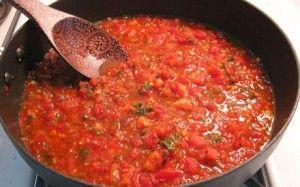 Tomatensaus maken met ui, look, verse kerstomaten, zwarte olijven, sambal, wijn en tomatenpulp uit een fles.