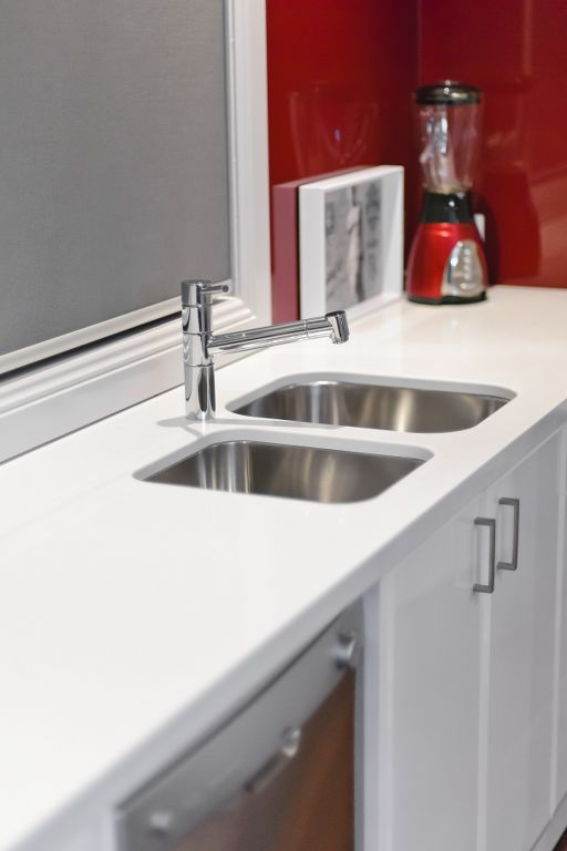 The Range - Custom Designed by Busby Homes. Caesarstone bench tops with stainless steel inset sinks and a feature red glass splashback.