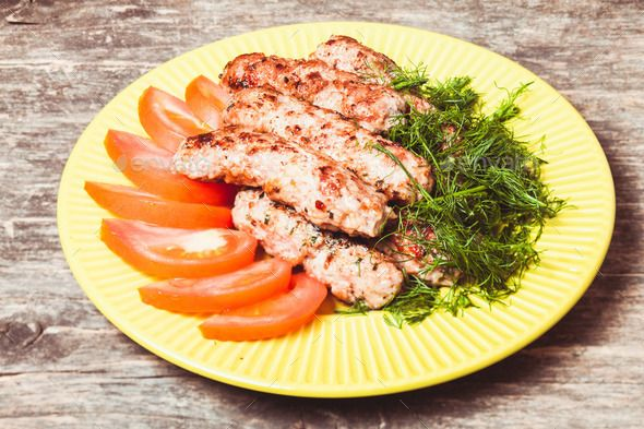 minced meat kebab with green dill and tomatoes on a plae