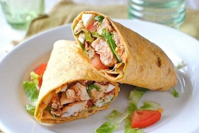 Buffalo Chicken Wrap from Tropical Smoothie Cafe (recipe makes one) - 1 large flour tortilla. 8 oz grilled chicken strips, 1 cup cut/shredded romaine lettuce, 1/4 cup tomatoes, 1/4 cup shredded mozzarella cheese, 1 tablespoon buffalo wing dipping sauce, 1 tablespoon ranch. Mix all ingredients together on open tortilla. Fold (closing both ends) and toast for 30 seconds - 1 minute.