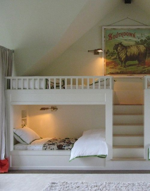 A stairway makes for easy access to the top bunk beds built into this children's attic room.