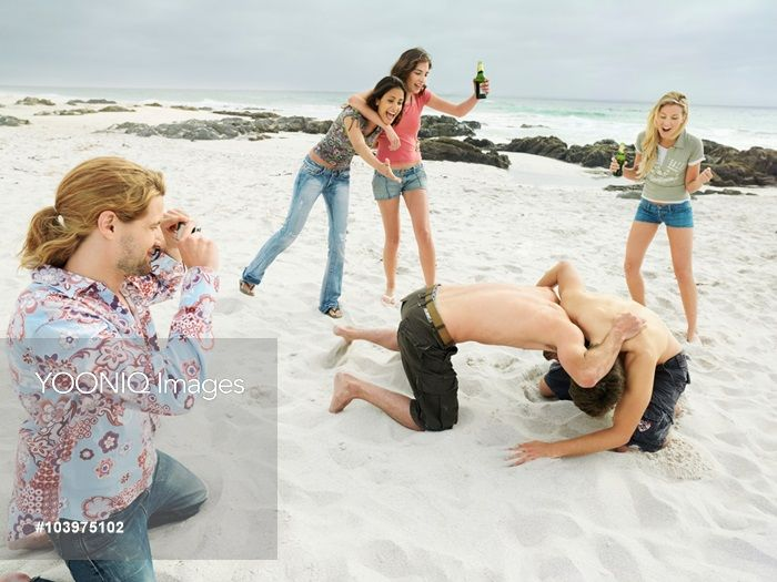 Yooniq images - Men Wrestling on Beach While Friends Watch