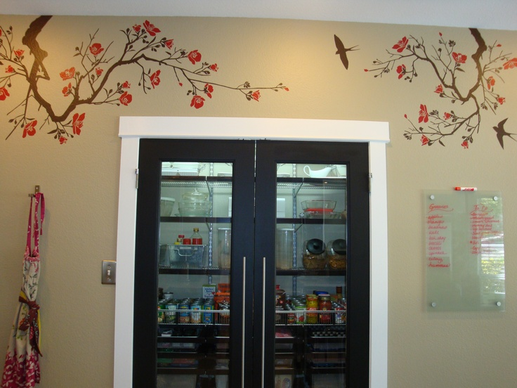 The Pantry.  The pantry is always organized so we have no issues having clear glass doors.  The Elfa system inside sure does make it look great!  The wall art we got from Etsy.  I made the reversible apron on the left. The glass message board we got at Ikea.