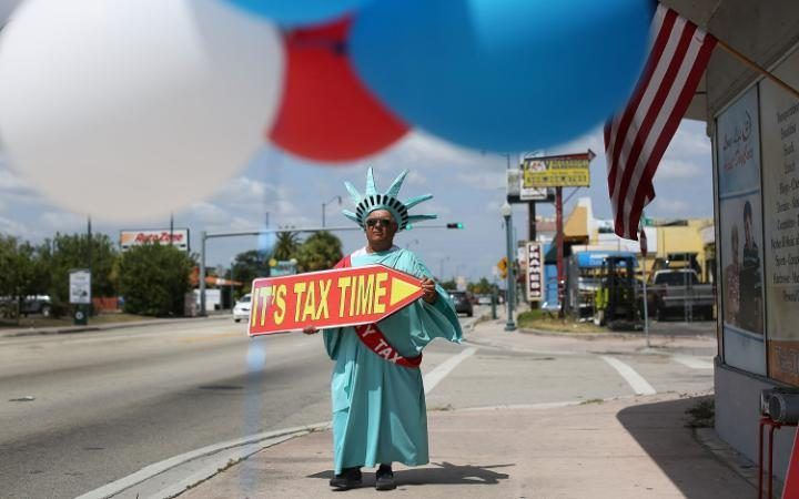 Armando La Rosa directs people to the Liberty Tax Service office as the deadline to file taxes looms in Miami, Florida. The Internal Revenue Service moved the deadline from April 15th to Monday the 18th due to the Emancipation Day holiday in Washington, D.C.