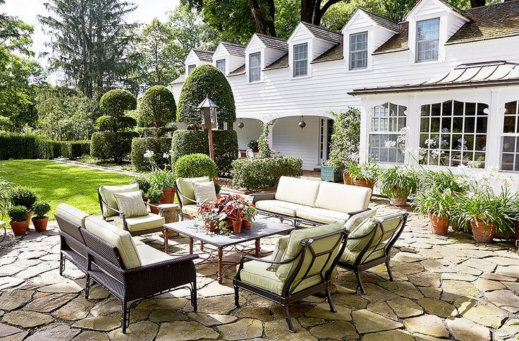 A stone terrace just off the main house was transformed into an outdoor room with comfy sofas designed by Bunny along with chairs in matching cushions. Groupings of terracotta planters help round out a lush, lived-in ambience. The tall topiary yews date to 1910.