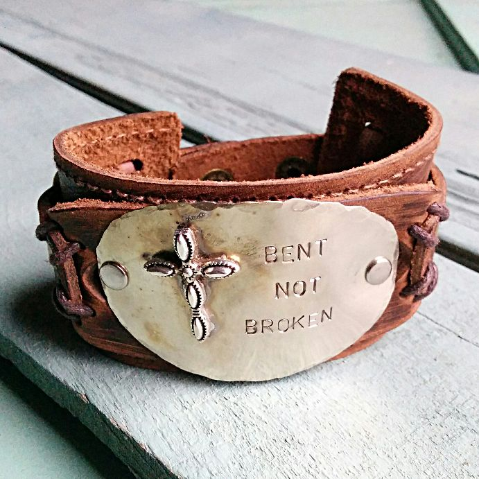 "Bent Not Broken Distressed Leather Cuff Bracelet features a hand stamped plate attached with two nickel rivets. Genuine leather cuff measures 2"" x 9"" Adjustable to 7"" and 7.5"" Disc measures approx. 1."
