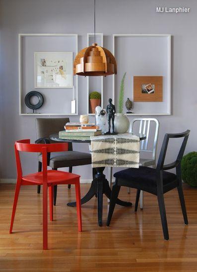 Разные стулья, круглый стол, серая стена и красный и черный стул, интересные рамы картин