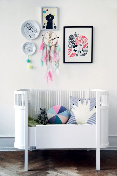 Modern nursery with a wall art collection and an open crib