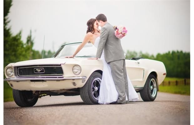 Alyssa and Stuart McGibbon share a tender moment near a vintage Mustang convertible.