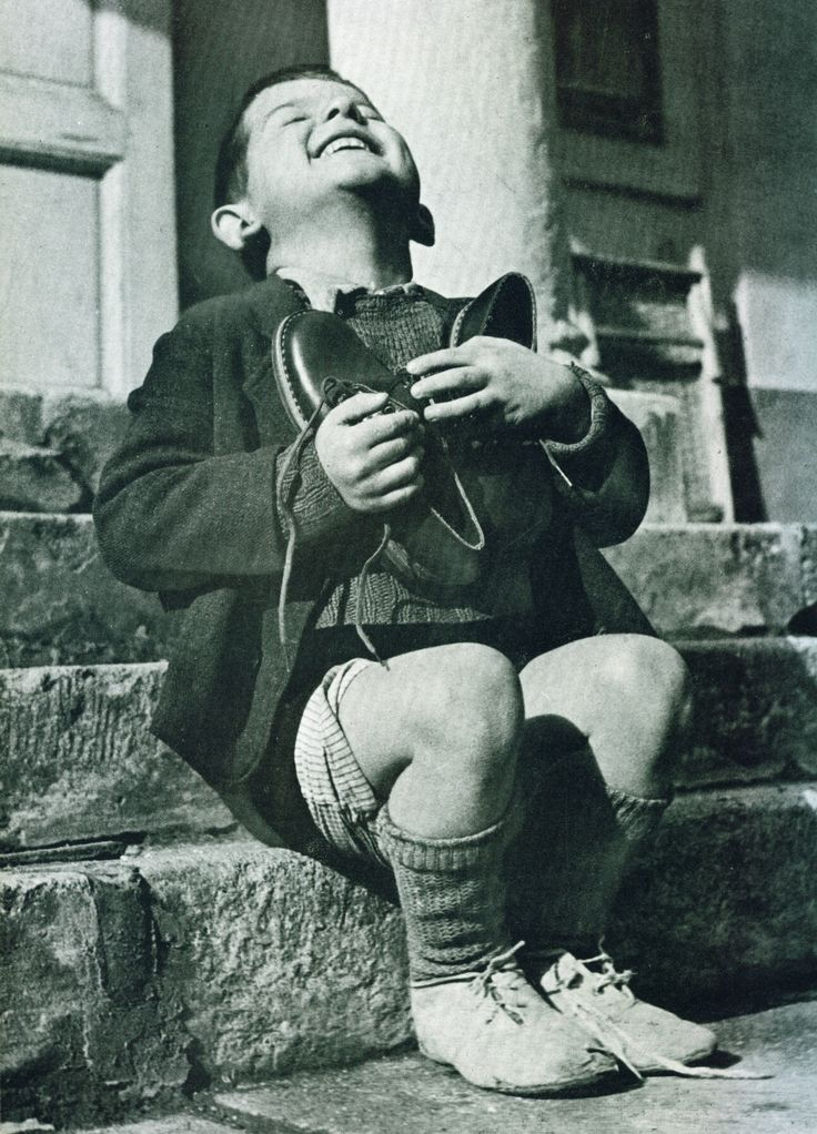 A 6 year-old boy, living in an orphanage in Austria rejoices and hugs a new pair of shoes given to him by the American Red Cross. (1946)