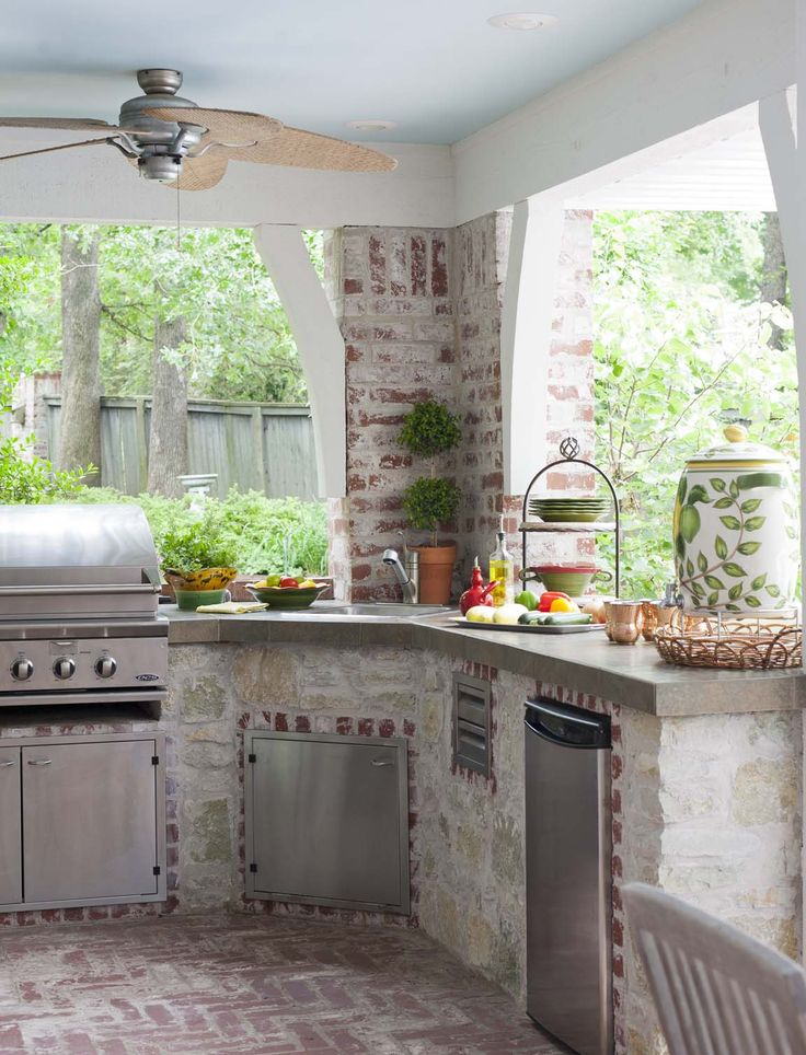 With a built-in grill, prep sink and below-counter refrigerator, there's no need to head inside for a snack—or even to cook dinner. Friends can gather around the bar, while the hosts fire up the grill.  The ceiling is painted Benjamin Moore's Bird's Egg.