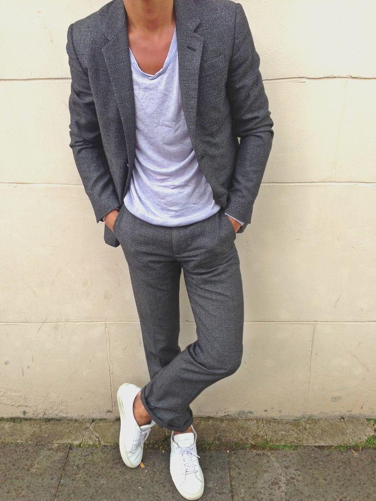 Acheter la tenue sur Lookastic:  https://lookastic.fr/mode-homme/tenues/costume-gris-fonce-t-shirt-a-col-rond-gris-baskets-basses-blanc/13158  — T-shirt à col rond gris  — Costume gris foncé  — Baskets basses blanches